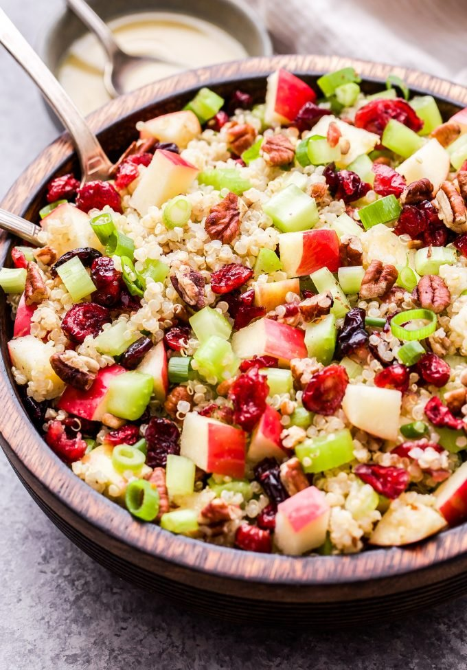 Cranberry Apple Quinoa Salad in wooden bowl with serving spoons. Small bowl of vinaigrette behind the salad.