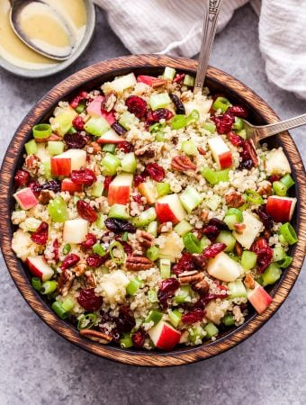 Cranberry Apple Quinoa Salad in wooden bowl with serving spoons. Small bowl of vinaigrette and a dish towel behind the salad.