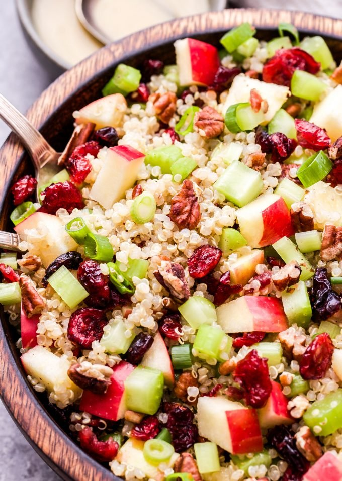 Cranberry Apple Quinoa Salad in wooden bowl with metal serving spoons.