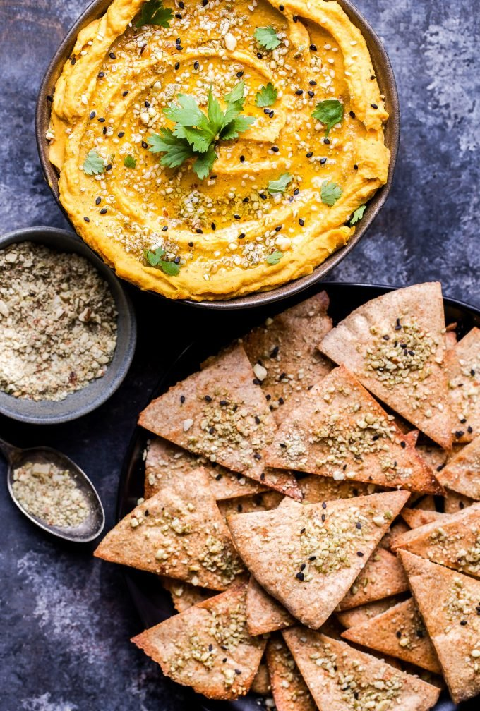Butternut Squash Hummus in a bowl topped with dukkah and cilantro. A small bowl of dukka and pita chips next to the hummus.