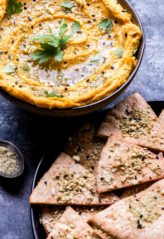 Butternut Squash Hummus in a bowl topped with dukkah and cilantro. Pita chips next to the bowl.