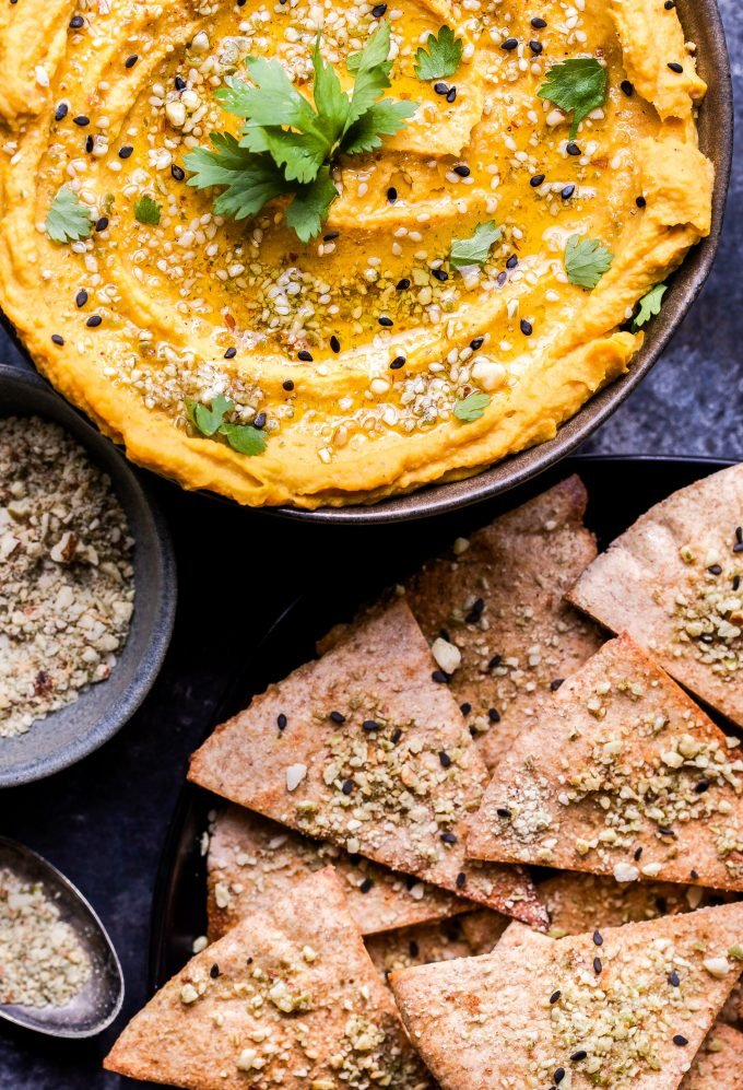 Butternut Squash Hummus in a bowl topped with dukkah and cilantro. Pita chips and a spoonful of dukkah next to the bowl