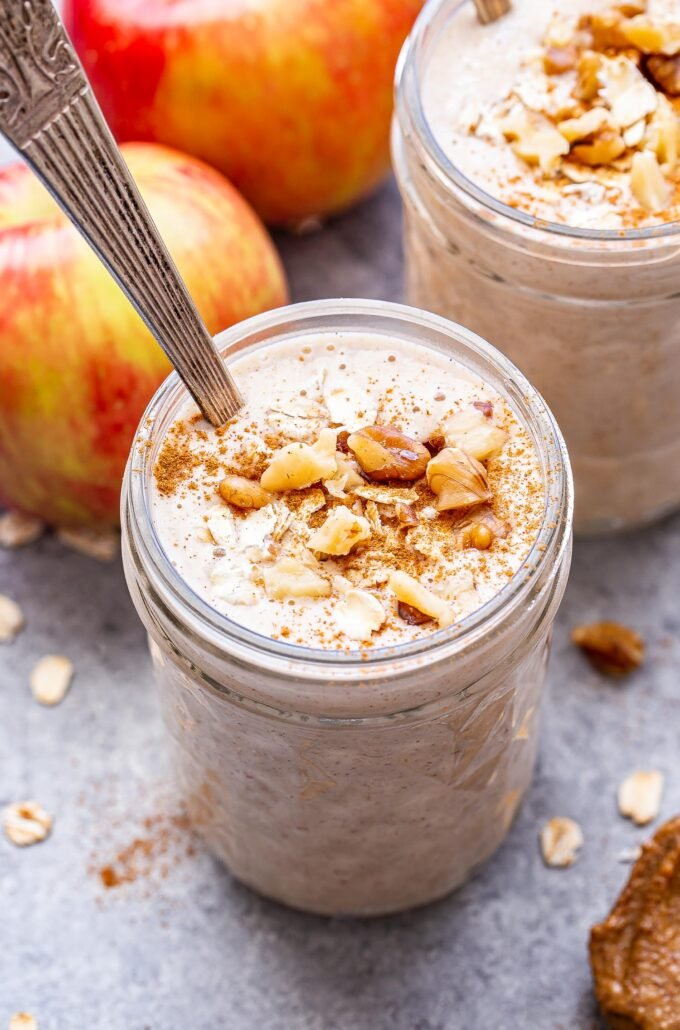 Overhead photo of two cinnamon apple smoothies in glass jars topped with oats, cinnamon and walnuts. Two apples behind the smoothies. Oats and cinnamon scattered around them.