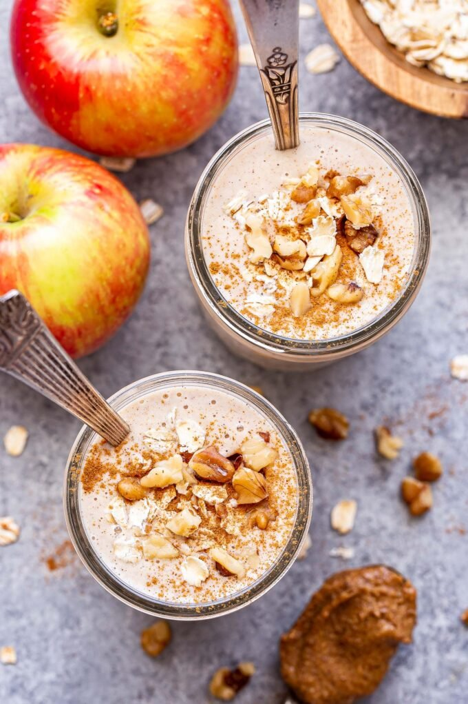 Overhead photo of two cinnamon apple smoothies in glass jars topped with oats, cinnamon and walnuts. Two apples behind the smoothies.