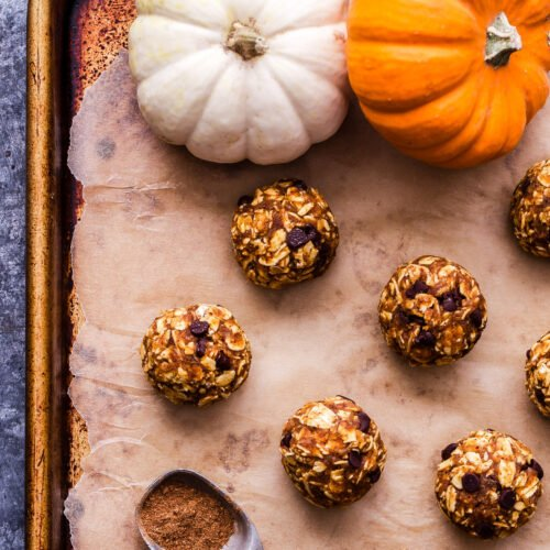 Pumpkin Pie Energy Bites on a parchment paper lined sheet pan with mini pumpkins and a teaspoon with pumpkin pie spice in it.