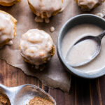 Overhead photo of Mini Chai Muffins with Vanilla Bean Glaze on parchment paper with a teaspoon of chai spice in front of them and a bowl of the glaze next to them.