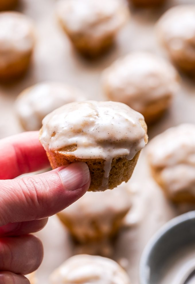 Hand holding one of the Mini Chai Muffins with Vanilla Bean Glaze