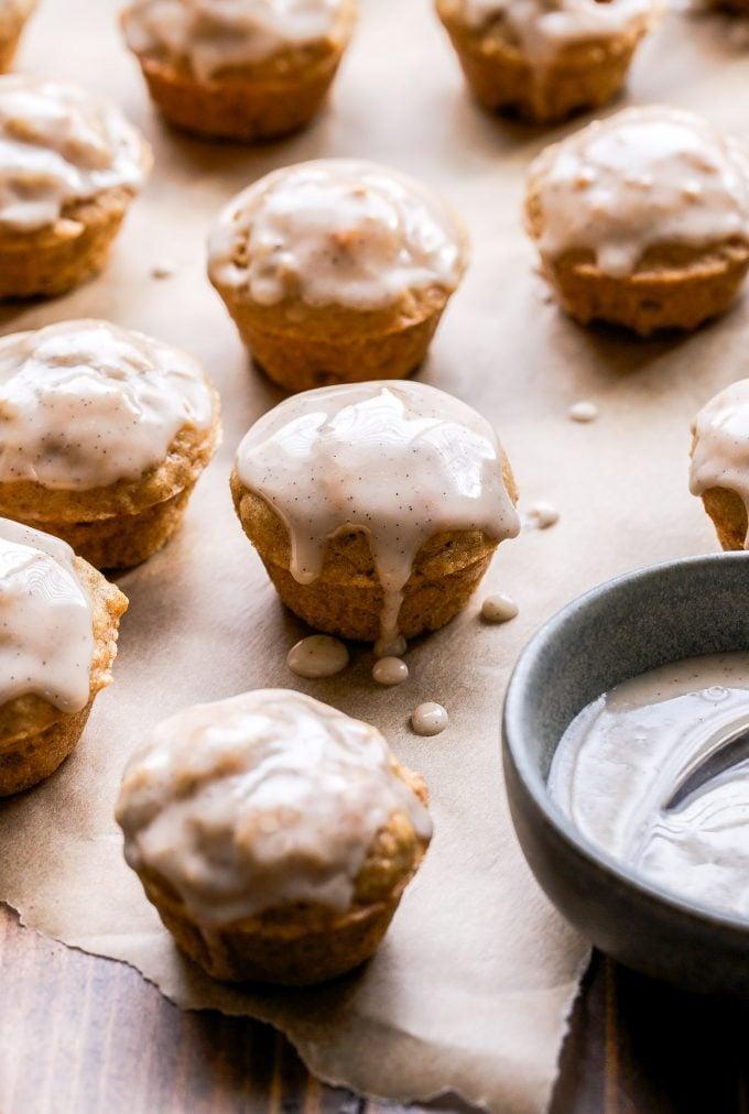 Mini Chai Muffins with Vanilla Bean Glaze on parchment paper.