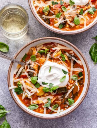 Overhead photo of two white bowls filled with lasagna soup. Soup topped with shredded mozzarella a big dollop of ricotta cheese and parsley leaves. Glass of white wine behind one of the bowls of soup.
