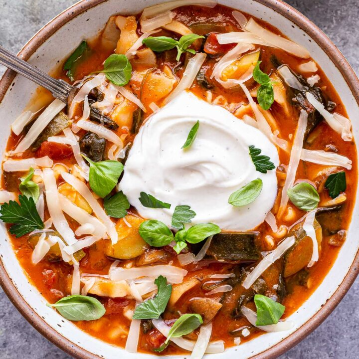 Overhead photo of vegetarian lasagna soup with melted mozzarella cheese and a big dollop of ricotta cheese on top.