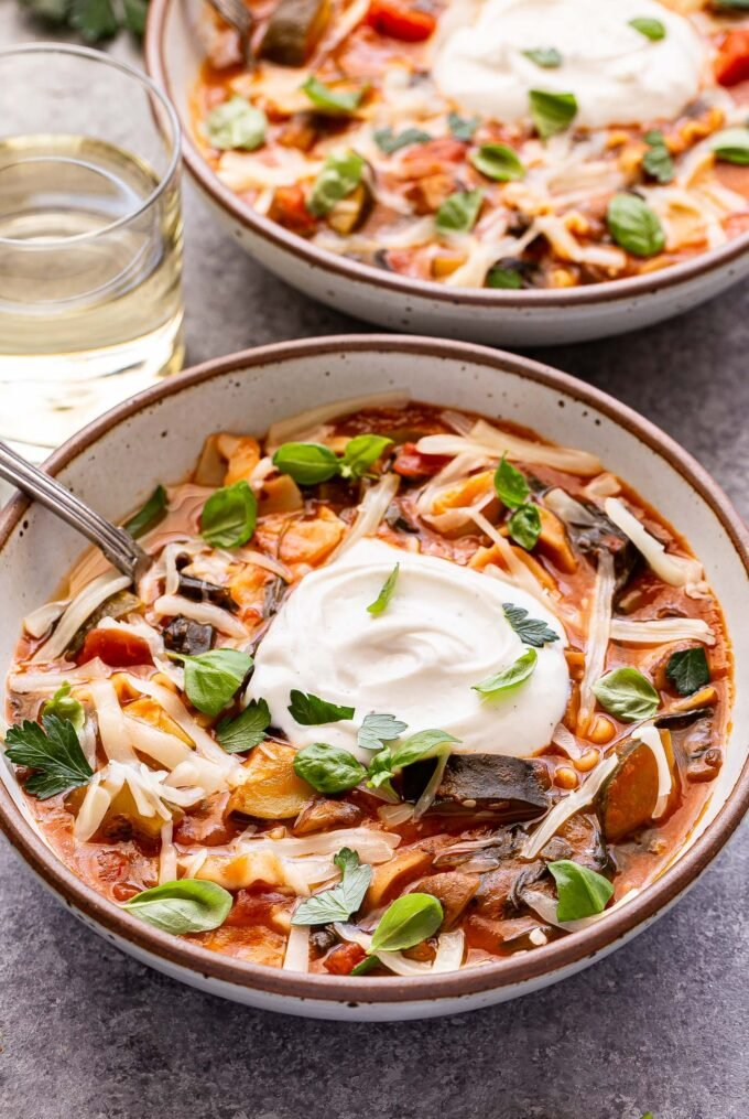 Two bowls of vegetarian lasagna soup topped with melted mozzarella, ricotta and parsley leaves. The bowl in front has a spoon in it and a glass of white wine behind it.