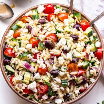 Greek Orzo Salad with tomatoes, olives and cucumbers in a round serving bowl with spoons and a bowl of vinaigrette behind it.