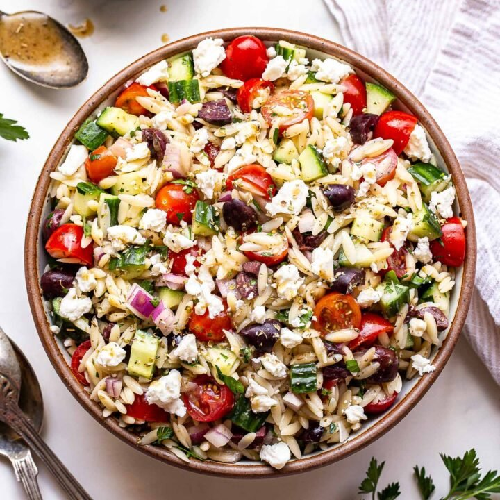 Greek Orzo Salad with tomatoes, olives and cucumbers in a round serving bowl with spoons next to it a bowl of vinaigrette and dish towel behind it.