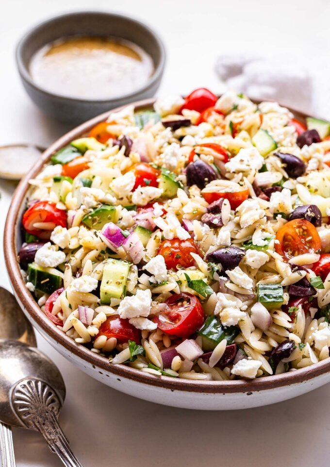 Greek orzo salad made with tomatoes, cucumber, feta, olives and red onion in a round white serving bowl with a small gray bowl of vinaigrette behind it.