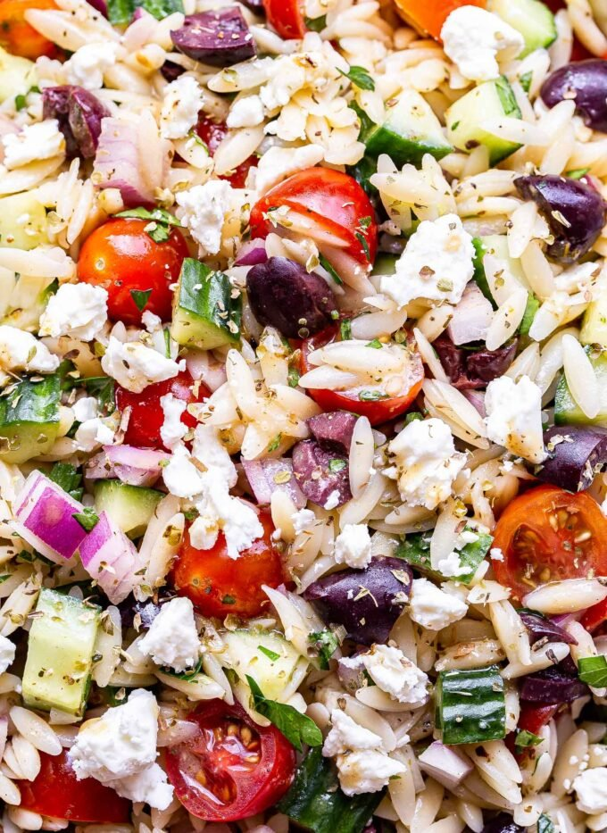 Closeup photo of Greek orzo salad with tomatoes, olives, cucumber, feta, red onion and parsley.
