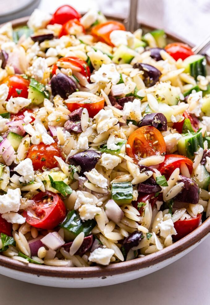 Closeup photo of Greek orzo salad with tomatoes, olives, cucumber, feta, red onion and parsley in a white serving bowl with spoons in the bowl.