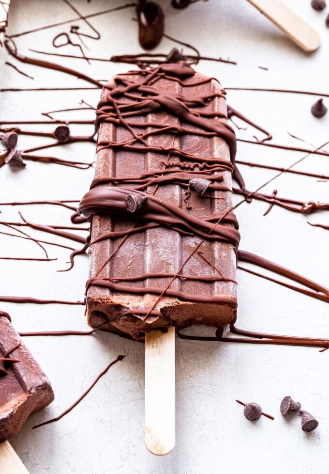 One Greek Yogurt Fudgesicle with melted chocolate drizzled over it.