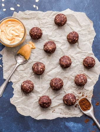 12 Peanut Butter Mocha Energy Bites on parchment paper with a spoon and jar of peanut butter.