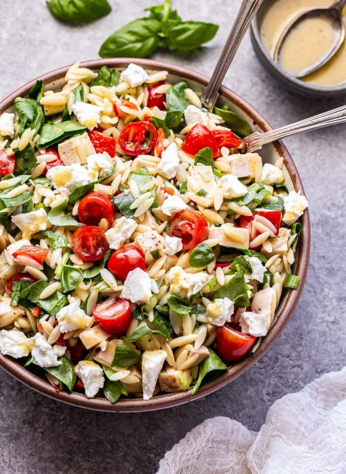 Overhead photo of Spinach Orzo Chicken Salad with Goat Cheese in a bowl with serving spoons in it. A bowl of vinaigrette and some basil leaves behind the salad bowl.