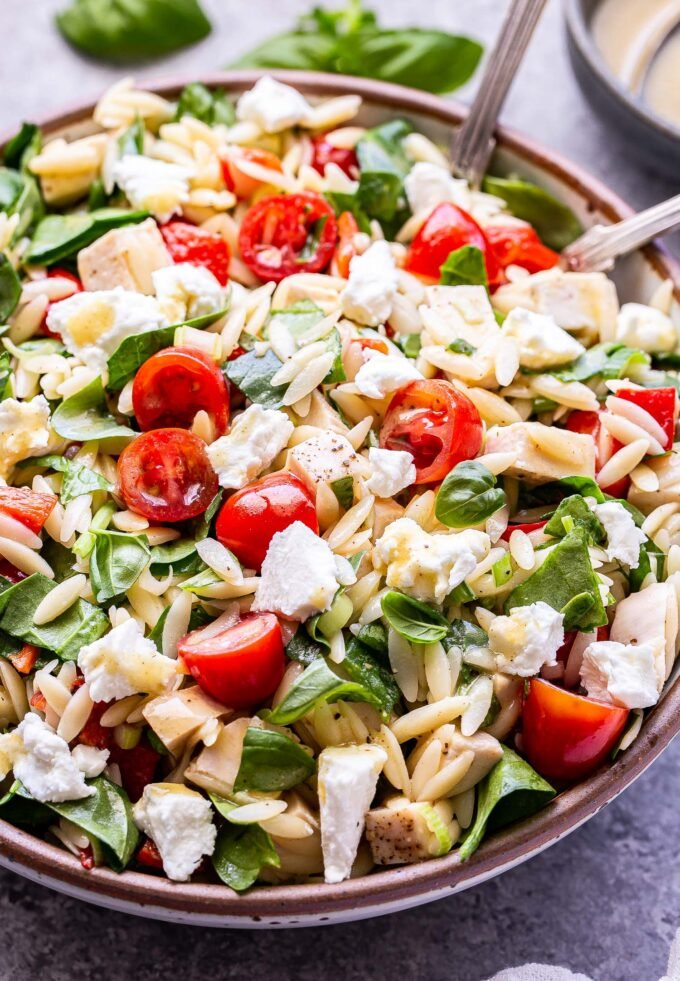 Spinach Orzo Chicken Salad with Goat Cheese in a white serving bowl with serving spoons in the bowl.