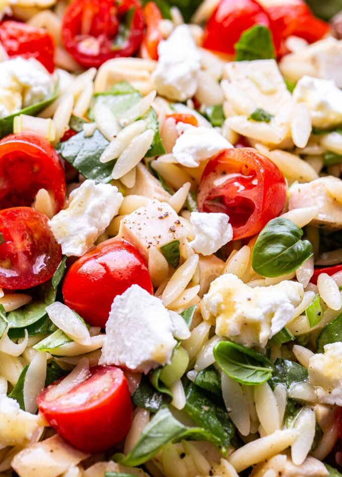 Closeup photo of Spinach Orzo Chicken Salad with Goat Cheese, halved cherry tomatoes, and roasted red peppers.