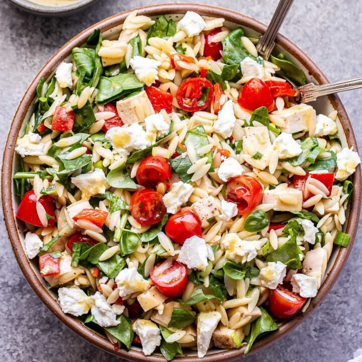 Spinach Orzo Chicken Salad with Goat Cheese, cherry tomatoes and roasted red peppers in a bowl with serving spoons.