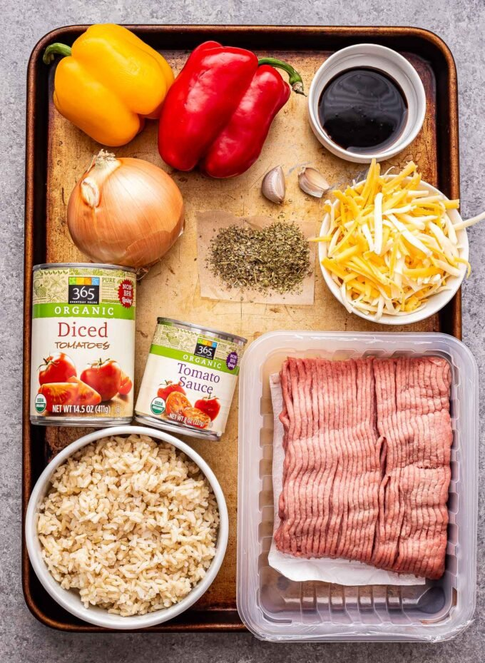 Overhead photo of a sheet pan full of the ingredients needed to make stuffed pepper casserole. Ground turkey, rice, peppers, onion, spices, shredded cheese, tomatoes sauce and diced tomatoes.