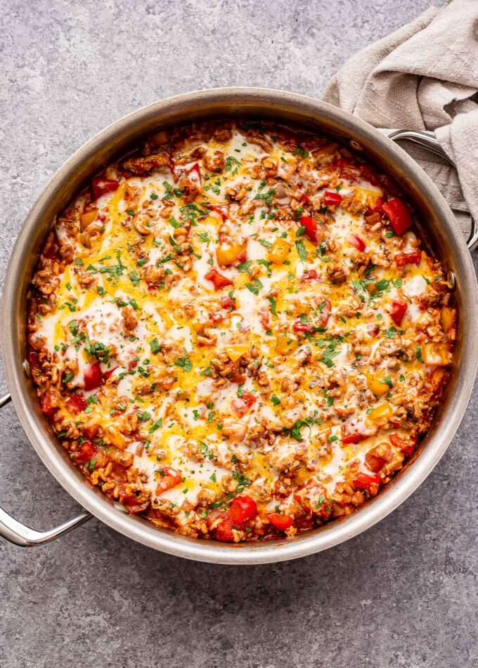 Overhead photo of a metal skillet full of the stuffed pepper casserole. It's made with ground turkey, rice, tomato sauce, red and yellow bell peppers and topped with melted cheese.