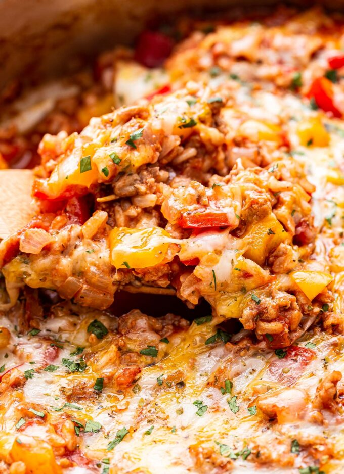 closeup photo of a wooden spoon holding some of the ground turkey stuffed pepper casserole with melted cheese on top.