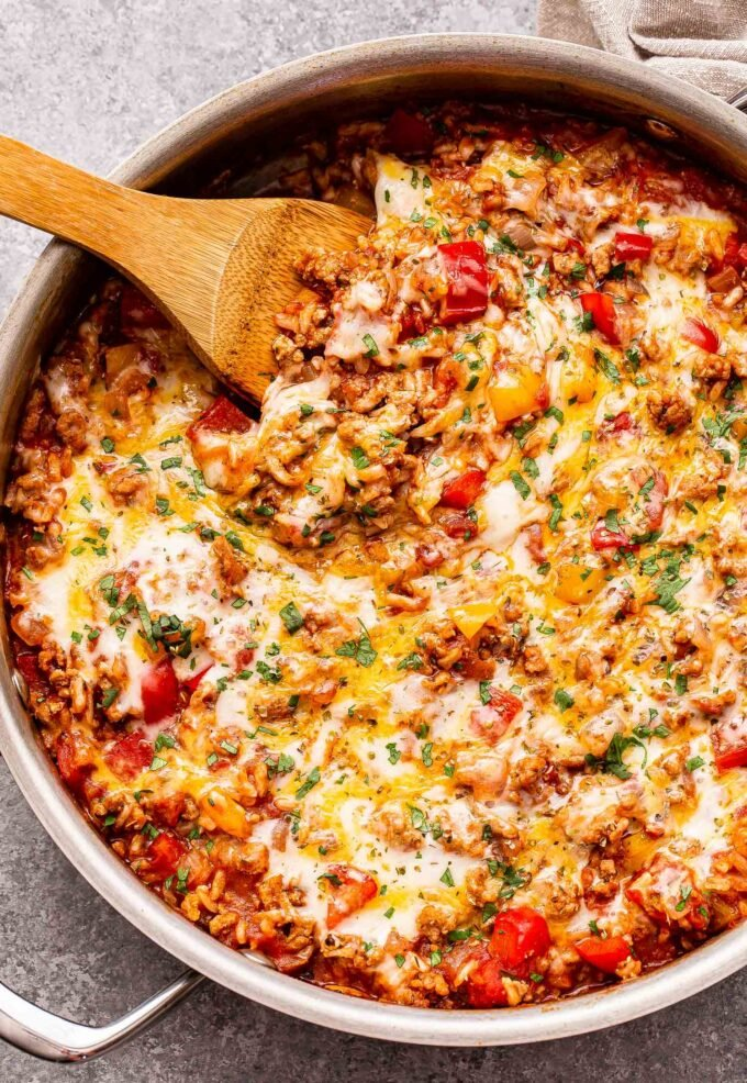 Overhead photo of a metal skillet full of the stuffed pepper casserole. It's made with ground turkey, rice, tomato sauce, red and yellow bell peppers and topped with melted cheese. A wooden serving spoon is in the skillet.