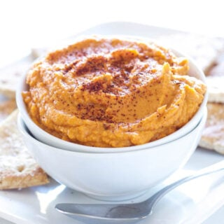 Sriracha Pumpkin Hummus in a white bowl with pita chips behind it.