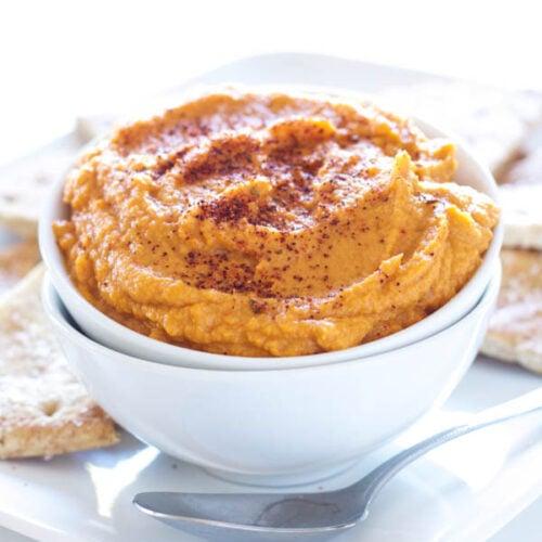 Sriracha Pumpkin Hummus in a white bowl with pita chips behind it.