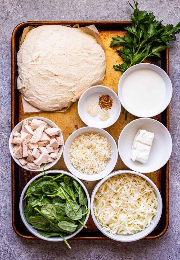 Chicken Alfredo Pizza ingredients on a sheet pan.