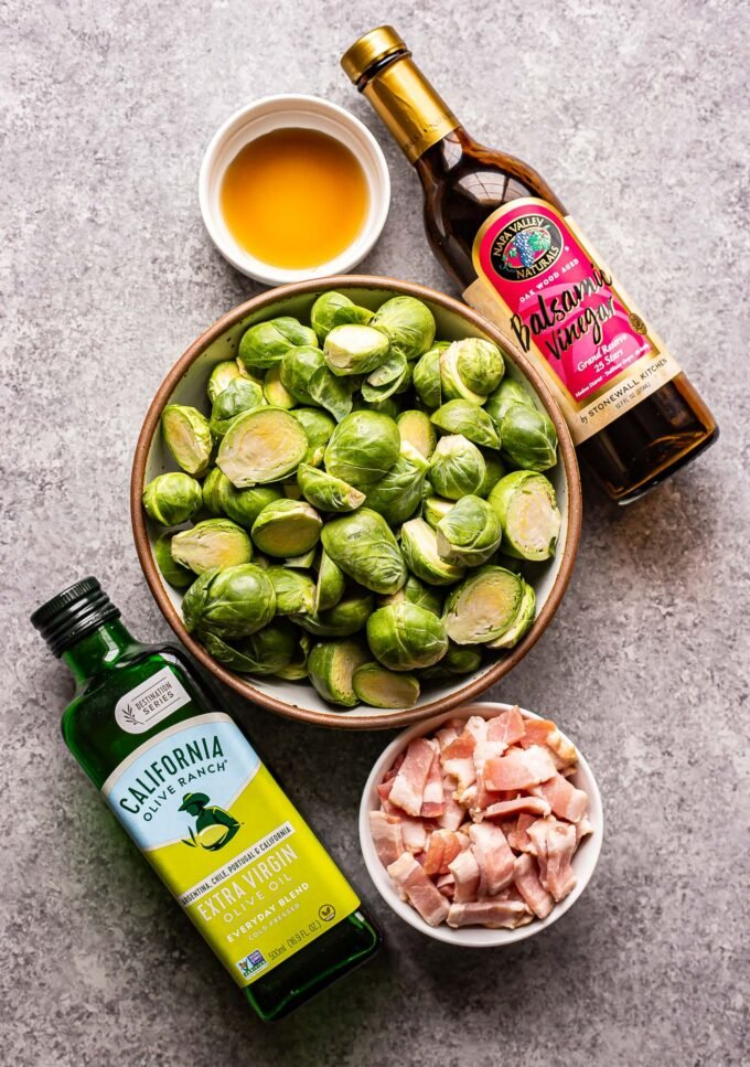 Ingredients photo showing brussels sprouts, bacon, maple syrup, balsamic vinegar and olive oil.