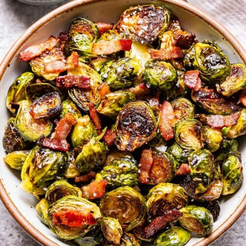 Overhead photo of a white bowl filled with balsamic maple roasted brussels sprouts with bacon. A small bowl of balsamic vinegar with a spoon in it behind the bowl.