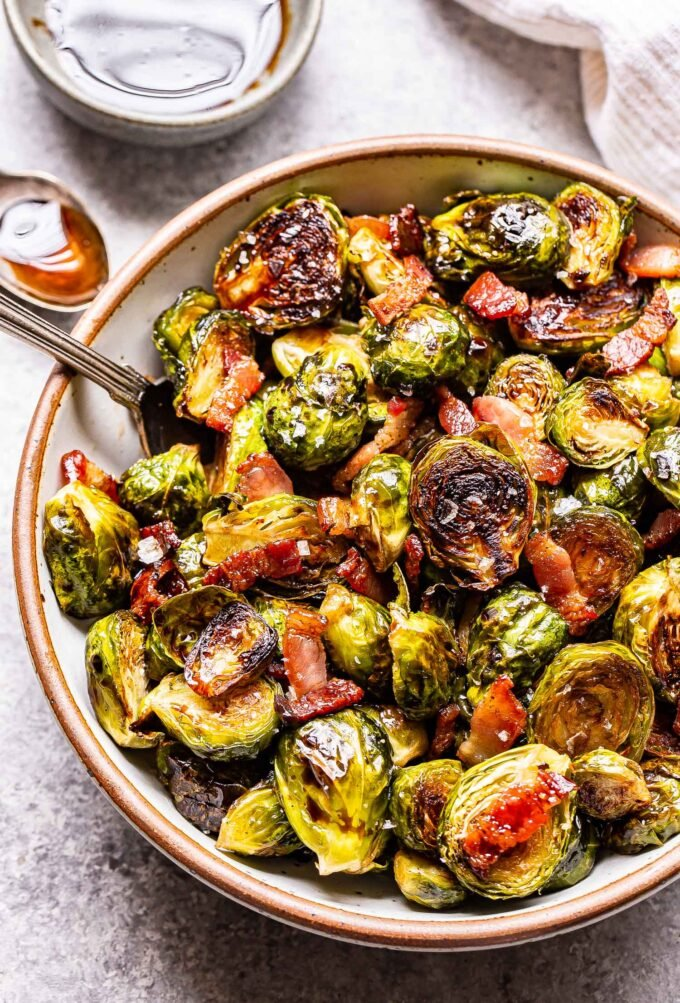 Overhead photo of balsamic maple roasted brussels sprouts with bacon in a white bowl with a spoon.