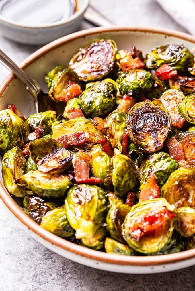 balsamic maple roasted brussels sprouts with bacon in a white bowl with a spoon. A small bowl of balsamic vinegar behind the bowl.