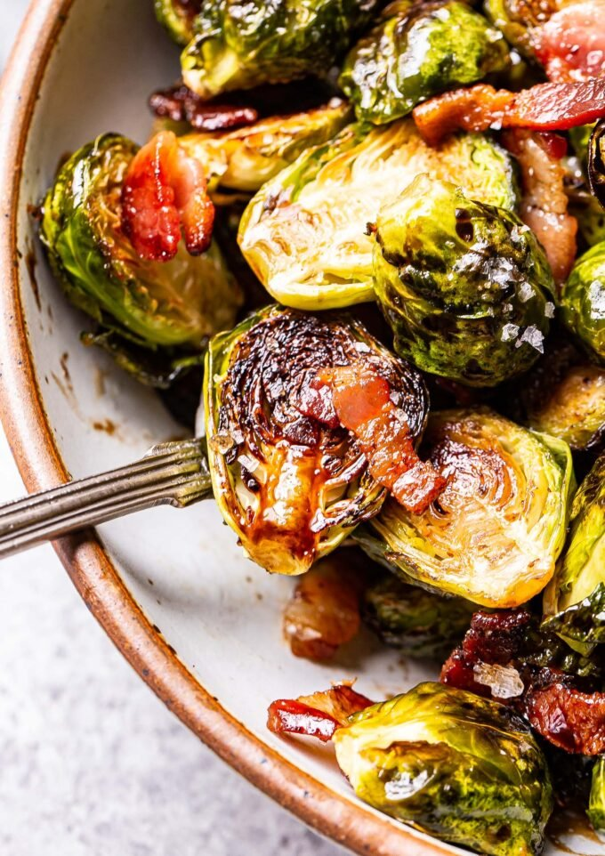 closeup photo of balsamic maple roasted brussels sprouts with bacon in a white bowl with a spoon.