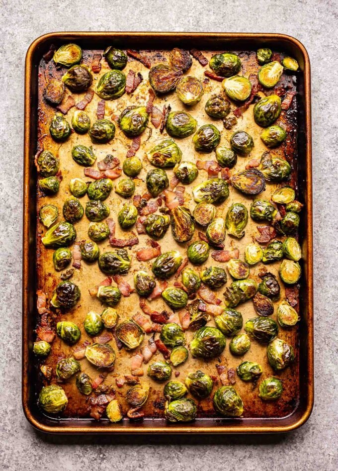 Roasted brussels sprouts and bacon on a sheet pan.