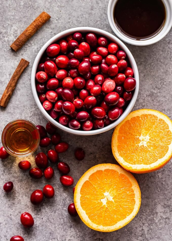 Ingredients used to make the Bourbon Orange Cranberry Sauce. Fresh cranberries, cinnamon sticks, an orange, maple syrup and bourbon.