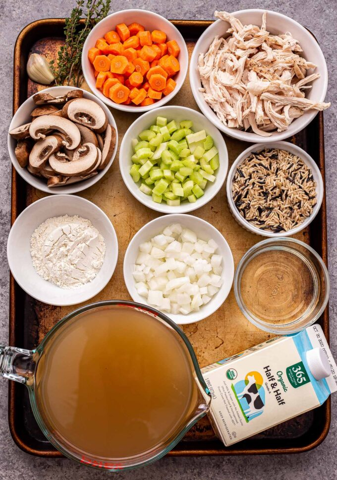 Overhead photo of the ingredients to make chicken and wild rice soup on a rimmed sheet pan.