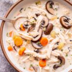 Overhead photo of a white bowl filled with creamy Chicken and Wild Rice Soup with a spoon in the bowl. Soup has sliced mushroom, shredded chicken, wild rice, carrots and celery in it.