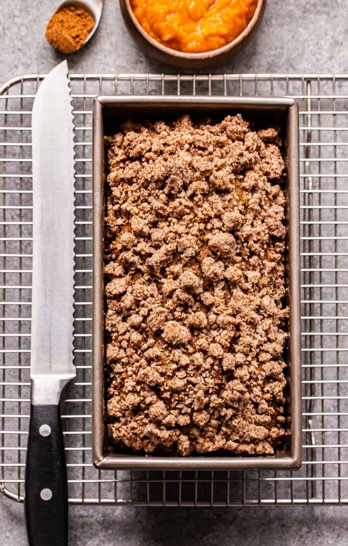 A loaf of Vegan Pumpkin Streusel Bread in the loaf pan on a cooling rack with a bread knife next to it.