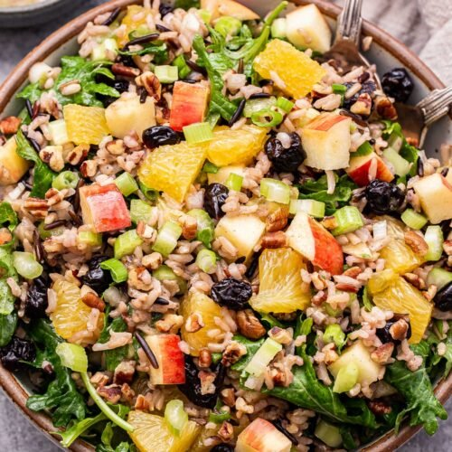 Winter Kale and Wild Rice Salad in a serving bowl with spoons