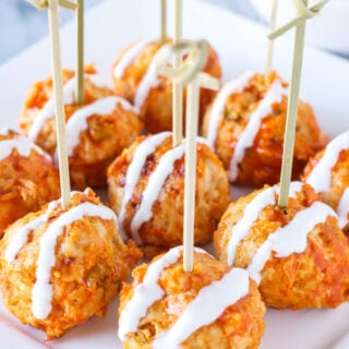 Square white plate filled with buffalo chicken meatballs with toothpicks in them. Meatballs are drizzled with blue cheese dipping sauce.