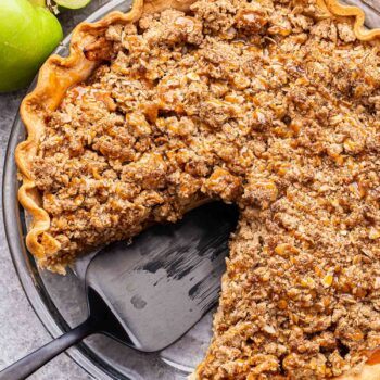 Caramel apple crumb pie in a glass pie plate with a piece cut out and a black spatula in it's place.