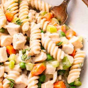 Closeup photo of Chicken Pot Pie Pasta in a white bowl with a fork in it.
