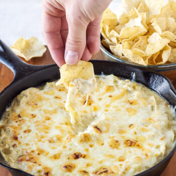 Someone dipping a tortilla chip into a skillet filled with green chile chicken enchilada dip. Melted cheese being pulled up with the chip.