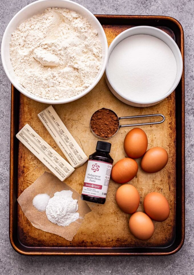 Ingredients used to make vanilla and chocolate pizzelles on a sheet pan.
