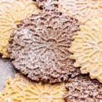 vanilla and chocolate pizzelles scattered on top of each other and dusted with powdered sugar.